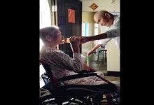 elderly husband gives water to his wife-min